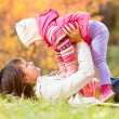 Happy mother and kid girl play outdoors in fall — Stock Photo #55039469