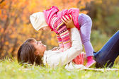 Happy mother and kid girl play outdoors in fall — Stock Photo