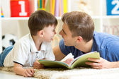 Father and his kid son reading a book on floor at home — Stock Photo