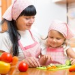 Woman and her kid daughter preparing vegetables at kitchen — Stock Photo #55307659
