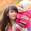 Portrait of beautiful mother and child girl outdoors in fall — Stock Photo #55307669