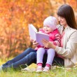 Mother reading a book to kid outdoors in fall — Stock Photo #55307677
