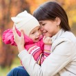 Portrait of beautiful mother and kid girl outdoors in autumn par — Stock Photo #55307689