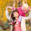 Beautiful mother with kid girl walking outdoors in autumnal park — Stock Photo #55307701