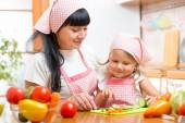 Woman and her kid daughter preparing vegetables at kitchen — Stock Photo