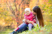 Beautiful young mother and her daughter have fun sitting at autu — Foto de Stock
