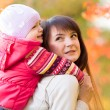 Beautiful mother with kid girl outdoors in fall — Stock Photo #55641271