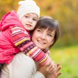 Happy mother with kid girl outdoor in autumn park — Stock Photo #55641305