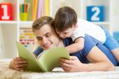 Father and his son read a book on floor at home — Stock Photo