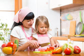 Mother and kid girl cook and cut vegetables on kitchen — Stock Photo