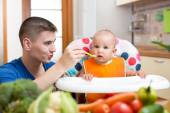 Young dad feeding his baby at kitchen — Stock Photo