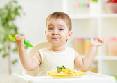 One year old kid boy in a highchair for feeding with a fork and — Stock Photo
