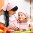 Mom and her daughter preparing vegetables at kitchen — Stock Photo #56511133