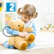 Cute little girl playing doctor with plush toy at home — Fotografia Stock  #57345463