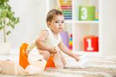 Kid boy sitting on chamber pot with toilet paper — Stock Photo