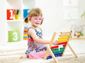 Child girl with eyeglasses playing abacus toy — Stock Photo