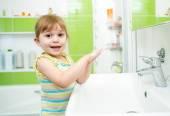 Cute little girl washing in bathroom — Stock Photo