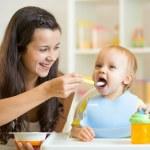 Mum spoon feeding child son — Stock Photo #57747775