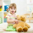Child girl playing doctor with plush toy at home — Stock Photo #57747909