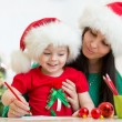 Kid girl and mother writing letter to Santa — Stock Photo #57980621