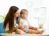 Female pediatrician examining of toddler kid with stethoscope — Stock Photo