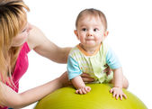 Mother doing gymnastics with baby on fit ball — Stock Photo