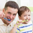 Father and child brushing teeth in bathroom — Stock Photo #58237061