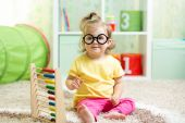 Child with eyeglasses playing abacus — Stock Photo