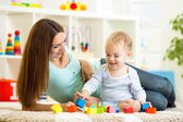 Cute mother and her son playing together indoor — Stock Photo