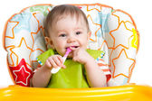 Happy baby child sitting in chair with a spoon — Stock Photo