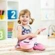 Little girl playing guitar — Stock Photo #58697763