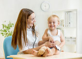 Pediatrician doctor examining of kid with stethoscope — Stock Photo