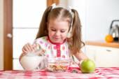Kid preparing corn flakes with milk — Stock Photo