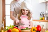 Mother and daughter cooking and cutting vegetables on kitchen — Stock Photo