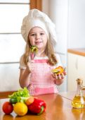 Child girl in cook hat eating vegetables — Stock Photo
