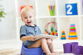 Child sitting on chamber pot playing tablet pc — Stock Photo