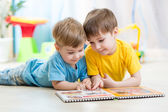 Kids brothers read a book at home — Stock Photo