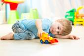Child boy toddler playing with toy car — Stock Photo