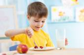 Kid eating healthy food at home — Stock Photo