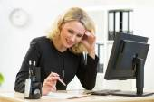 Smiling business woman looks at document sitting at table in office — Stock Photo