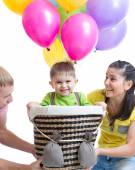 Family play at birthday party and playing with son in flight on a makeshift balloon — Stock Photo