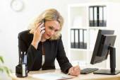 Business woman working in office. Worker talking by phone and writing by pen — Stock Photo