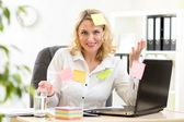 Businesswoman overwhelmed with sticky reminder notes — Stock Photo
