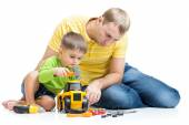 Child and his dad repair toy tractor — Stock Photo