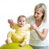 Mother doing gymnastic to kid on fitness ball — Stock Photo