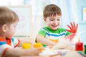 Smiling kids playing and painting — Stock Photo