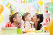Parents kiss their son celebrating child birthday — Stockfoto