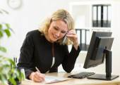 Smiling middle-aged business woman working in office — ストック写真