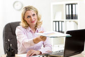Smiling mature businesswoman giving paper — Stock Photo