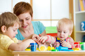 Kids and mother playing colorful clay toy — Stock Photo